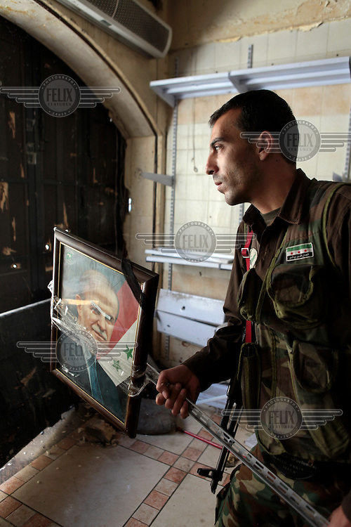 A Free Syrian Army fighter holds a photograph of Hafez al-Assad, the father of Bashir al-Assad, that he has taped to a pole. He plans to wave it at snipers in the hope of taunting them into shooting it before they regonise it...Protests against the regime of Bashar al-Assad erupted in March 2011. Although initially peaceful, they were violently repressed by the Syrian army and police. In response to being ordered to shoot unarmed civilians, large numbers of men deserted and formed the core of the Free Syrian Army (FSA) which was soon joined by civilian volunteers. Since early 2012 the protest movement has escalated into an armed uprising that many consider a civil war. Sustained fighting is ongoing throughout Syria between the regular army and its allied militias and the Free Syrian Army as well as other anti-regime groups, some of which include foreign jihadists.