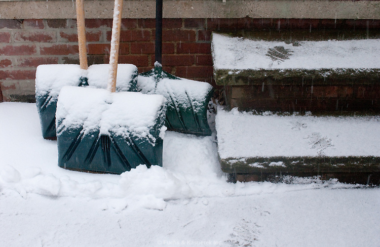 The collection of shovels sit outside the back door of a home in winter.