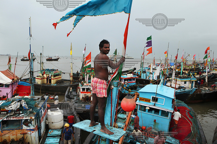 A fisherman on top of his boat in Sassoon Dock after returning from a fishing trip lasting several weeks in the Indian Ocean. The fresh catch is sold on the spot. The bigger fish, shrimps and prawns are sold to export companies. Fish production in India has increased more than fivefold since independence making it one of the world's leading seafood exporting nations..