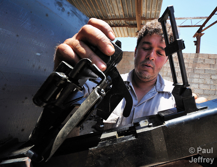 A rebel mechanic in Misrata, Libya, checks the mechanism of a heavy machine gun he has mounted on the back of a pickup truck for use against government troops loyal to strongman Moammar Gadhafi.