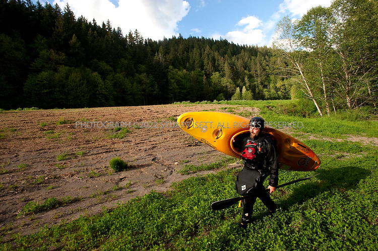 5/18/2009--Sandy, OR, USA..Kayaker Paul Kuthe carries his kayak towards a recently opened stretch of the Sandy River in Oregon. The Marmot Dam was removed from the river in 2007 allowing fish and kayakers to travel the newly opened stretch of water...©2009 Stuart Isett. All rights reserved.