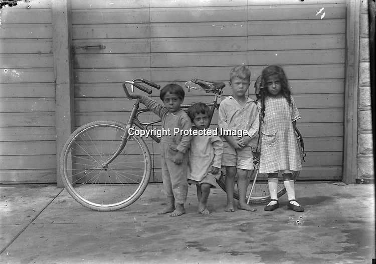 ZAKEM CHILDREN AND FRIENDS, C. 1921. After this photograph was featured in NEWSWEEK magazine in November 1999, collection owner Douglas Keister received a call from a radiologist in Atlanta, Georgia. The man, who identified himself as Jim Zakem said the child on the left was his father and provided additional information. Lebanese-born Alexander K. Zakem (1879-1942) and his wife Anise were the parents of the three dark-haired children. James, born in Michigan in 1917, is at left beside little sister Lillian. The blond boy was a playmate. Older sister Adeline, at right, was born in Montreal in 1916. <br /> <br /> Zakem immigrated to America in the 1890s and came to Nebraska around 1900. When his first wife died, he returned to Lebanon, remarried, and came back to Nebraska in 1918-1927, joining relatives who had settled in the area. He operated restaurants in Lincoln and smaller Nebraska communities. James Zakem, a retired electrical engineer in Michigan, shared the family history in 2000.<br /> <br /> Photographs taken on black and white glass negatives by African American photographer(s) John Johnson and Earl McWilliams from 1910 to 1925 in Lincoln, Nebraska. Douglas Keister has 280 5x7 glass negatives taken by these photographers. Larger scans available on request.