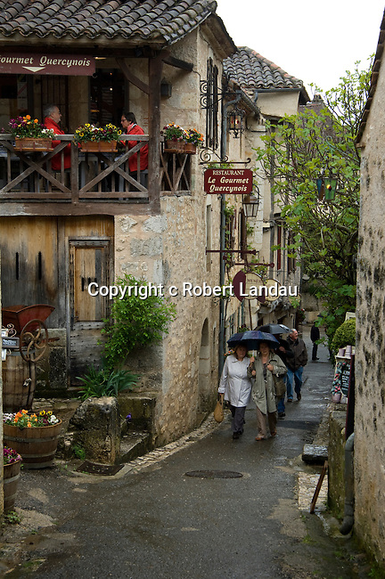 Visiots stroll the streets of St. Cirq Lapopie, Fraance