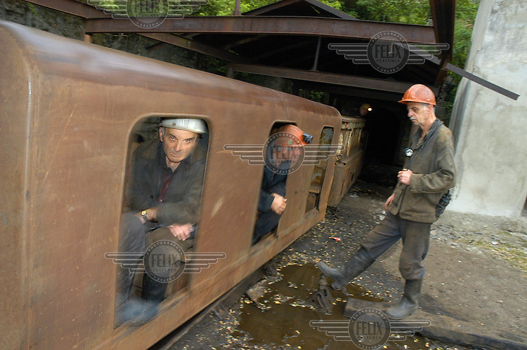 Coal miners at the Shakhta Imena Mindeli Mine ride a train into underground at the start of their morning shift .
