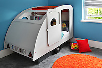 A play pod/caravan, with small cushions and bookshelves inside