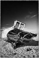 Wooden boat on the shingle beach at Dungeness, Kent, United Kingdom