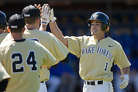 Steven Brooks #1 of the Wake Forest Demon Deacons high fives teammates following his solo home run in the 4th inning versus the Duke Blue Devils at Jack Coombs Field March 29, 2009 in Durham, North Carolina. (Photo by Brian Westerholt / Four Seam Images)