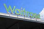 Green Waitrose supermarket shop sign against blue sky, Ipswich, Suffolk, England, UK