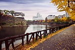 Walkway path along Osaka Castle Park inner moat canal with fortification walls and Osaka downtown city scenery in the background on colorful misty autumn morning. Chūō-ku ward, Osaka city, Japan 2017