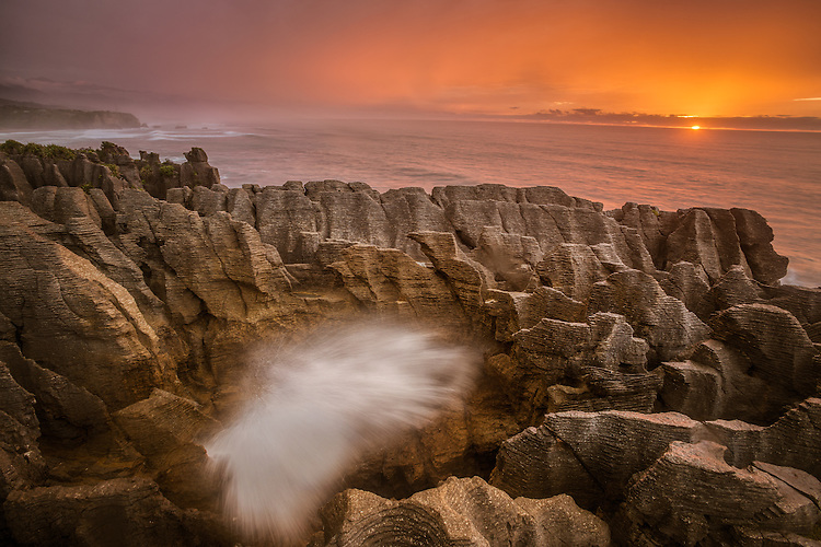 Photo of  sunset over the Tasman Sea with Putai Blowhole erupting in the foreground. Punakaiki / pancake rocks. West Coast New Zealand - stock photo, canvas, fine art print