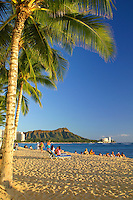 People of vacation  to Oahu enjoy the palm trees, white sand beaches of Waikiki and the spectacular view of Diamond Head Crater.