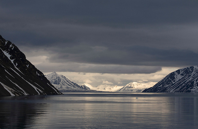 Looking along a cloudy Lilliehookfjorden to the sun shining on mountains in Krossfjorden. Spitsbergen