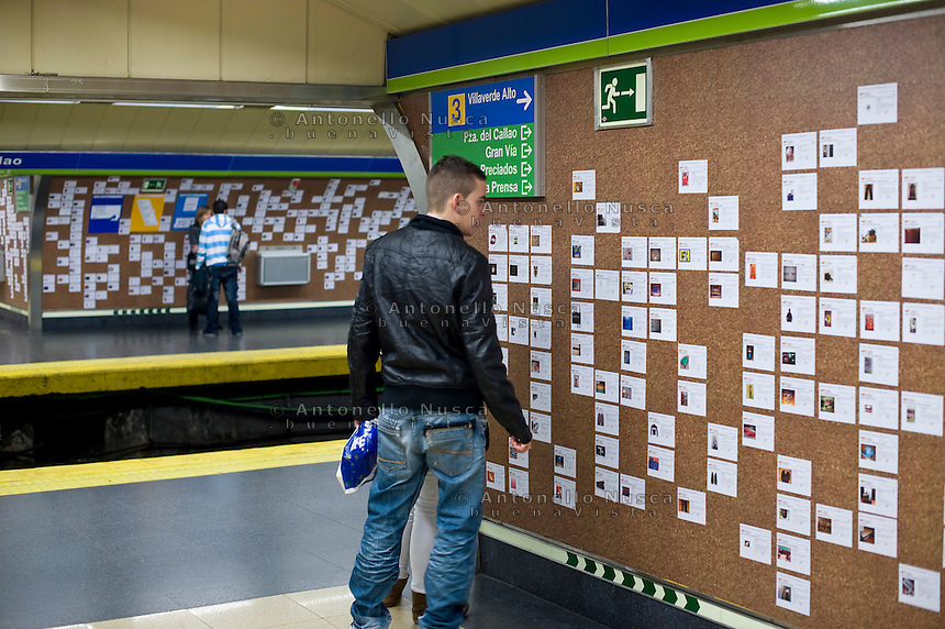 Un giovane legge annunci in una bacheca nella metropolitana di Madrid