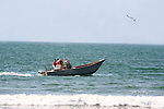 Men in small boat on the Pacific Ocean
