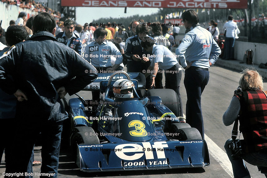 Jody Scheckter sits in the Tyrrell P34 six wheel Formula 1 car in the pit lane during practice for the 1976 Grand Prix race at Zolder, Belgium. Ken Tyrrell stands alongside the car on the right side of the frame.