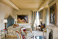 Renaissance style paintings and antique furniture in a pale blue and gold theme are a feature of one of the bedrooms at Borgo Santo Pietro in Tuscany