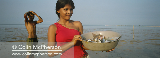 A young girl holds up a bowl of freshly caught fish from the Tapajos river in the Amazonian basin. Villagers along the freshwater river lived from their catches and fruit and vegetable harvested from the rainforest. Catch numbers declined due to a severe drought in the Amazon and the effects of deforestation on river habitats as the rainforest was cleared by illegal logging and burning for cattle ranching and growing soy beans for export.