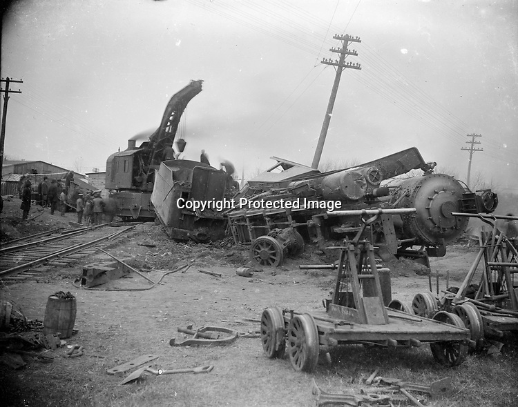 WRECK OF LOCOMOTIVE NO. 2040. While this scene includes human spectators in the left background, the photographer has positioned the camera so that the two handcars in the right foreground also appear to be observing the fallen steam engine. The derailed and toppled locomotive bears the name plaque 2040 on the front of the engine. One of the derailed cars in the background is painted with the initials CRI&amp;P of the Chicago, Rock Island and Pacific Railroad. A rail-mounted crane is in the process of lifting the tender away from its wrecked locomotive. Rock Island Railroad built its line through Lincoln in 1892, the last of several railroads to add service to Lincoln. Abandoned in the 1970s, the Rock Island right-of-way is now one of several bicycle trails through the city.<br /> <br /> Photographs taken on black and white glass negatives by African American photographer(s) John Johnson and Earl McWilliams from 1910 to 1925 in Lincoln, Nebraska. Douglas Keister has 280 5x7 glass negatives taken by these photographers. Larger scans available on request.