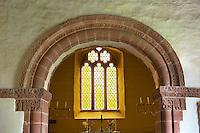 Norman Romanesque chancel arch of the church of St Peters, Rowlstone, Herefordshire, England. The relief sculptures on the capitals are attributed to the Herefordshire School of stonemasons. The style draws upon Anglo-Saxon and celtic designs. The chancel arch has rolled mouldings which is framed by a thin row of chip-carved triangles.