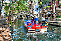 River boat on the San Antonio River walk on a nice fall day.  This is one of the most popular tourist attractions in the city since it is right downtown and their are tons of restaurants and hotels right along the river to stay at.