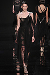 "Model walks runway in a one shoulder black Chantilly lace dress with embroidered strap detail from the Reem Acra Fall 2016 ""The Secret World of The Femme Fatale"" collection, at NYFW: The Shows Fall 2016, during New York Fashion Week Fall 2016."