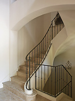 A cool stone staircase with a simple wrought-iron banister winds its way down through through the centre of the house