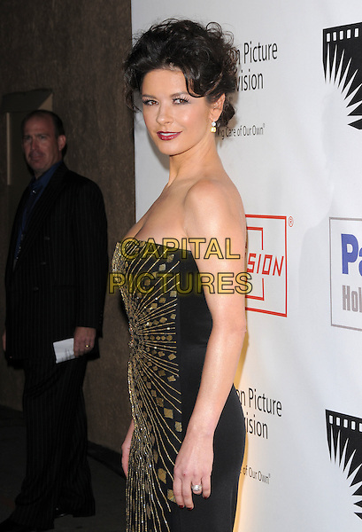"CATHERINE ZETA JONES .at The 4th Annual ""A Fine Romance"" held at Sony Picture Studios in Culver City, California, USA,  November 08 2008.                                                                     .half length strapless black gold print dress ring hair up .CAP/DVS.©Debbie VanStory/Capital Pictures"