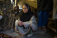 Shamima, 35, squats in her temporary shelter built using the shelter kit given to her by Save the Children, in Purnishadashah village, Jammu and Kashmir, India, on 24th March 2015. Shamina is a widow who's house fell down during the floods. Save the Children supported the family with emergency shelter items like tarpaulin and other emergency relief kits for household, education, non-food items, and food baskets. Photo by Suzanne Lee for Save the Children