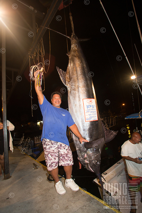 Bomboy Llanes, captain of the fishing boat Lana Kila, stands next to a Pacific blue marlin grander at Honokohau Harbor, Big Island; he and his crew used the Bomboy Lure he holds up to catch the 1,041-lb. fish.