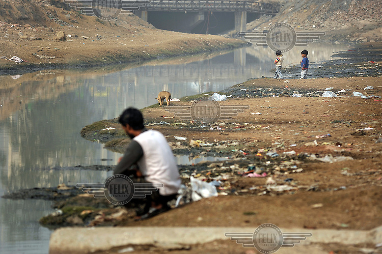 Small children, a dog and a man stand on the banks of a river in a slum in the area of Nizamuddin East.