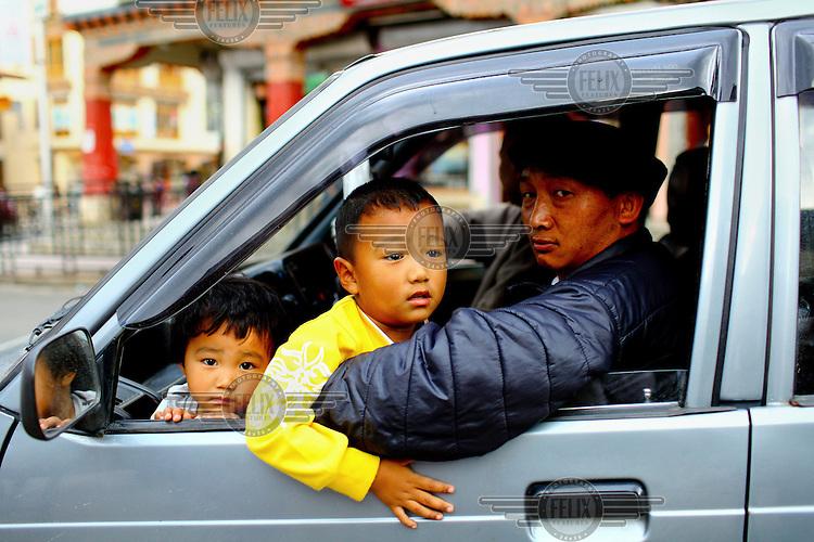 A family in their car on a street in Thimpu.