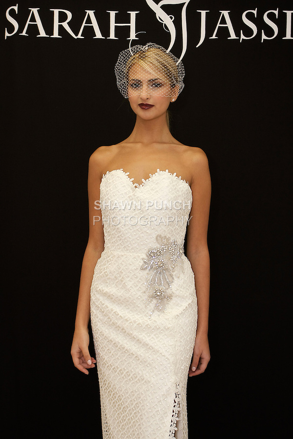 "Model poses in ""Rhea"" - a strapless guipure lace gown with crystal beaded applique and front slit, from the Sarah Jassir Fall 2013: From Concept To Creation collection, for her Angelique Bridal store opening at 6 East 45 Street, during New York Bridal Fashion Week, October 15, 2012"