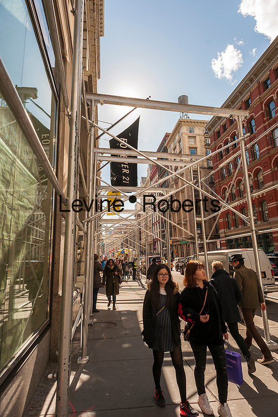 Visitors walk under an unfinished scaffold in the Soho neighborhood of New York on Wednesday, March 8, 2017.  (© Richard B. Levine)