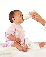 Young baby girl being bottle fed with milk