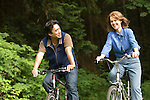 Couple riding bikes, laughing in wooded area