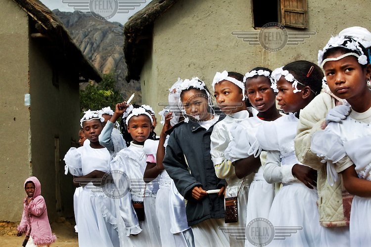 Children, dressed in their church clothes, on their way to Sunday service to receive Communion.