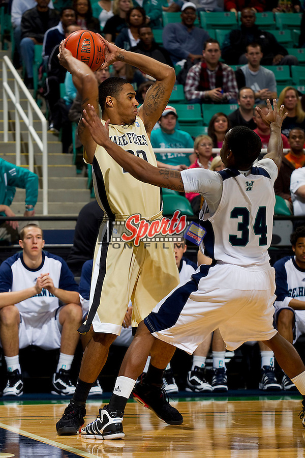 Ari Stewart #20 of the Wake Forest Demon Deacons looks for an open teammate as Ahmad Grant #34 of the UNC-Wilmington Seahawks defends at the Greensboro Coliseum on December 12, 2010 in Greensboro, North Carolina.  The Seahawks defeated the Demon Deacons 81-69. Photo by Brian Westerholt / Sports On Film