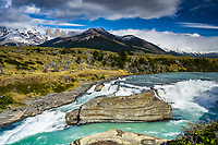The Rio Paine flows over a large waterfall in Torres Del Paine National Park, Chile as its famous towers rise in the background.