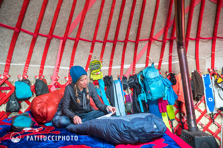 A woman reading inside a yurt while on a ski touring trip in Kyrgyzstan