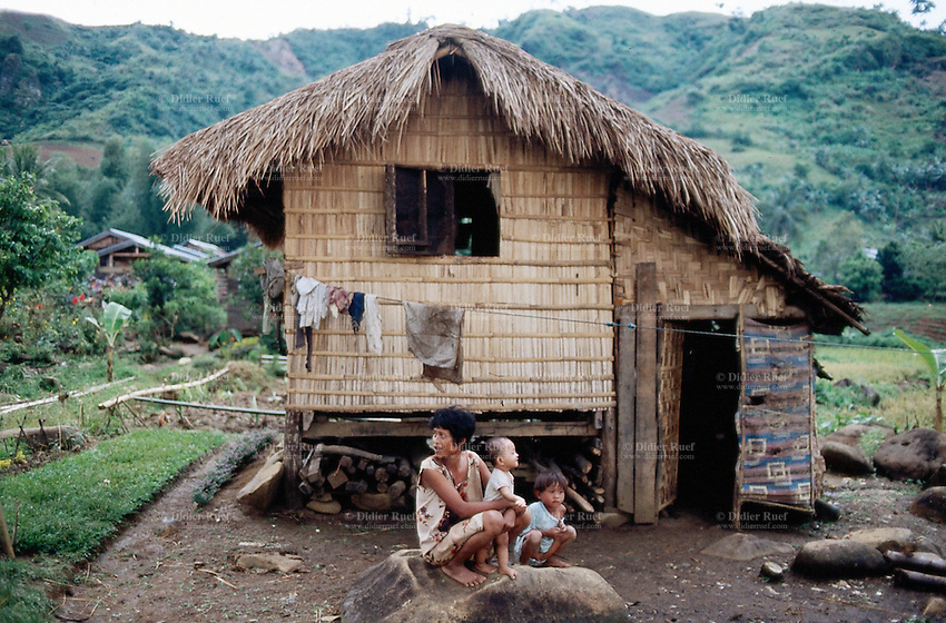 Philippines. Negros Island. Province of Negros Occidental, located in the  Western Visayas region. Barangay (village) Camao. A mother and her two children seat on a rock outside at the house. © 1999 Didier Ruef