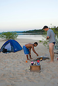 Pará State, Brazil. Xingu River. Patrick Cunningham and Gilson in camp, preparing food.