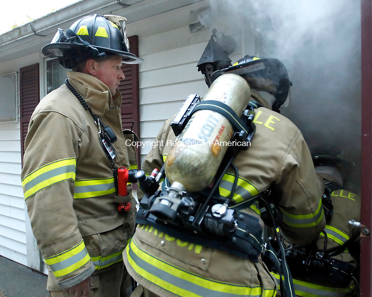 Terryville, CT-07 May 2012-050712CM05-  Terryville Volunteer Fire Department Captain Scott Poultun (left) instructs firefighters during a SCBA (self contained breathing apparatus) training exercise at a house next to the Terryville Chevrolet car dealership Monday night.  Volunteers firefighters from the department were subjected to a fog machine that simulated a real life smoke situation.   Christopher Massa Republican-American