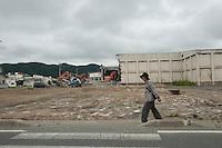 A landscape view of an old woman walking next to a street following the 311 Tohoku Tsunami in Ishinomaki, Japan  © LAN