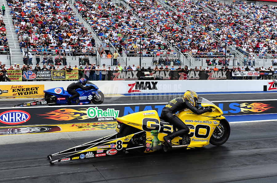 Sept. 18, 2011; Concord, NC, USA: NHRA pro stock motorcycle rider Karen Stoffer (near lane) races alongside Jim Underdahl during the O'Reilly Auto Parts Nationals at zMax Dragway. Mandatory Credit: Mark J. Rebilas-