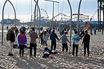 People enjoying playground on Santa Monica Beach near the pier.