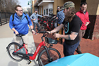 NWA Democrat-Gazette/DAVID GOTTSCHALK Blake Hasley (right), bike technician with VeoRide, assists Joe Simpson, a graduate student at the University of Arkansas, Tuesday, February 5, 2019, after Simpson took a demonstration ride on one of the new electronic-assist VeoRide bikes on the Frisco Trail section in Fayetteville. The bike-share program has added an additional 150 new electronic-assist bikes. The 150 will replace 50 of the former  teal bikes. The city of Fayetteville, University of Arkansas and Experience Fayetteville partnered to bring VeoRide to residents and students. Standard seven-speed bicycles and motor-assisted e-bikes are available in Fayetteville and on the campus at varying rates and plans.