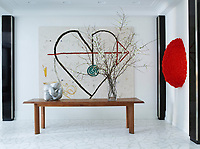 In the gallery entrance, the 1950s table is by Charlotte Perriand, and the red wall sculpture is by Lynda Benglis.