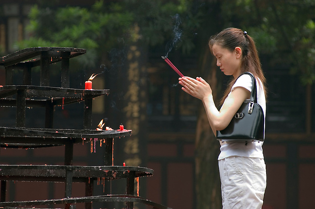 Chinese woman lights devotional candles at the Tang Dynasty Wenshu Monastery  - Sichuan Province, Chengdu, China