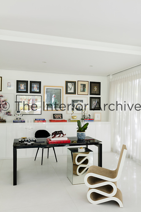 The home office is sparsely furnished with a simple desk and a Wiggle chair by Frank Gehry. A collection of artworks is displayed on the wall above a built-in cupboard unit.