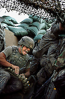 Specialist Brian Underwood shouts out to his gunner while preparing grenades during an attack on the American 'Restrepo' bunker by insurgents. The position was named after a soldier from 2nd Platoon who was recently killed by insurgents..Battle Company, 2nd Battalion Airborne of the 503rd US Infantry are undergoing a 15 month deployment in the Korengal Valley, epicentre of the war and scene of fierce fighting with the Taliban...